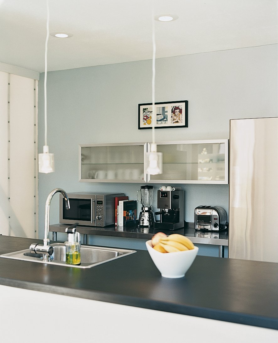 Kitchen, Pendant Lighting, and Metal Cabinet The Viking range and Bosch refrigerator in the kitchen are paired with Ikea lights and cabinets.  Photo 5 of 6 in Affordable Modern House Built with Sheer Determination