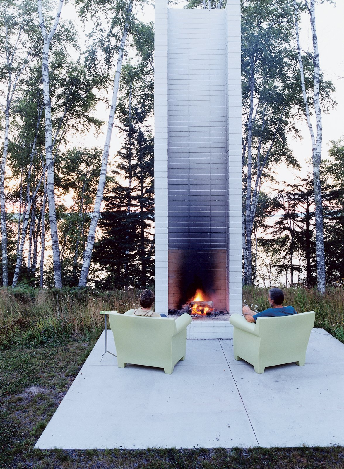 """Outdoor, Small Patio, Porch, Deck, Concrete Patio, Porch, Deck, Trees, Grass, and Back Yard Philippe Starck's outdoor chairs for Kartell provide cozy fireside seating. These and the sofa version were selected by Salmela. """"They're very much an art form,"""" he says.  Photo 15 of 19 in 18 Modern Fireplaces and Fire Pits to Inspire Outdoor Living from Off the Beaten Path"""