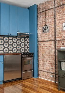 """In the kitchen, we changed the layout,"" Davison says. ""It was a galley kitchen, extending lengthways into the room. We spun it back along the back wall. The tiles are Moroccan concrete tiles that came from a supplier here in Manhattan. The idea was to inject some color and playfulness into the space with the blue cabinetry."" Photo by Alan Gastelum."