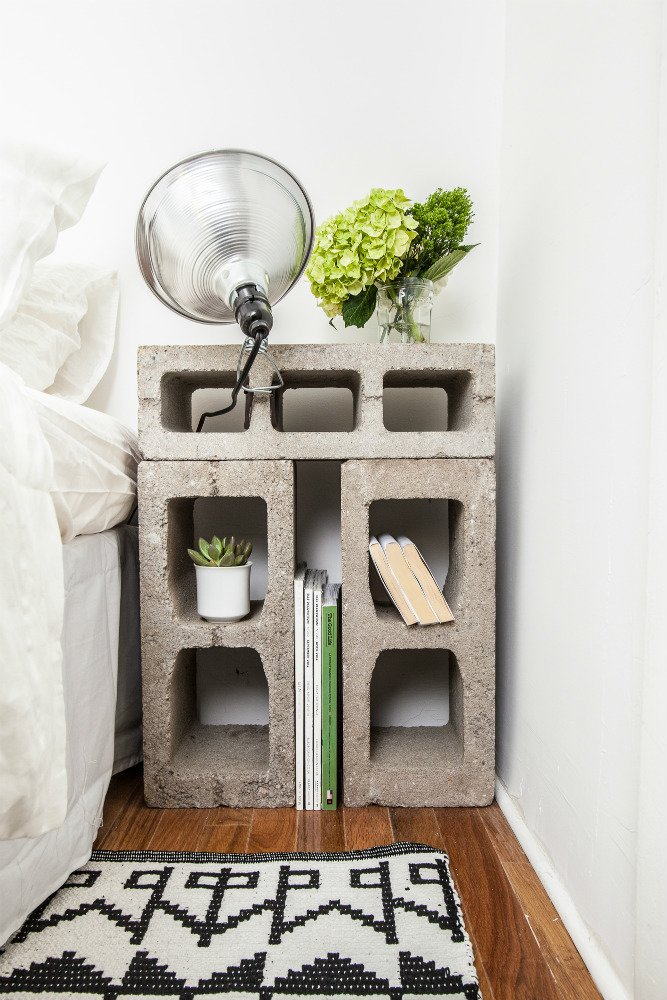 The nightstands were fashioned from concrete blocks that were rescued from the street outside the building. Photo by Alan Gastelum. Tagged: Bedroom, Medium Hardwood Floor, Rug Floor, Table Lighting, Bed, and Night Stands.  Photo 6 of 8 in A Gut Renovation Transforms a Tiny Manhattan Apartment