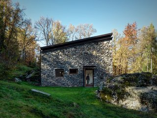 "Architect Alfredo Vanotti sourced the home's stone exterior from the woods behind the property. ""I believe that mountain architecture is an emblematic example of sustainable architecture,"" he says. Reinforced concrete stands behind the stone facade to provide insulation. Vanotti wanted to focus this project on the simple materials of concrete, natural larch, iron, and wood."