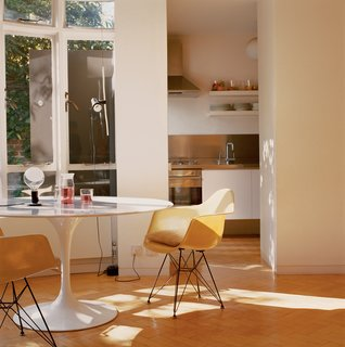 The kitchen spills out into the living room, where the focus is on a Saarinen Tulip table, Eames fiberglass shell chairs, and lamps by Achille Castiglioni.