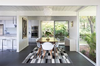 In an effort to create a more open floor plan, a portion of the wall between the kitchen, family area, and dining room was removed. Part of the dining room wall was also replaced with a huge window that not only makes a statement, but also gives the family a stunning view of the backyard area. Photo by Mariko Reed.