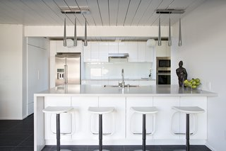The kitchen remodel included creating more space and installing a single-plane island that served as the perfect spot for the family's children to do everything from eating to studying schoolwork. Photo by Mariko Reed.