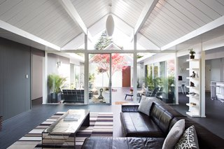 The classic gabled roof with exposed-ceiling rafters and tongue-and-groove paneling gives way to a central open courtyard at this Eichler home.