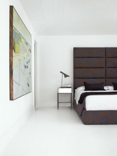 """The home's bedroom features a large headboard designed by Hill. """"I think a bedroom should be your go-to place for getting away from all the craziness,"""" Hill says. """"It should be very simple and warm."""" Photo by Gregory Miller."""