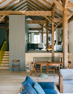 "A Passive House and ""Sauna Tower"" Join a 19th-Century Barn in the Hudson Valley - Photo 1 of 13 - The open living-and-bedroom area of Ian Hague's rural retreat can be divided by a wall that rises from within the master-suite platform. Interior designer Elaine Santos blended her client's collection of vintage furniture with no-fuss pieces like a Shaker-style bench by Ilse Crawford for De La Espada. <span style=""line-height: 1.8;"">The dining chairs are a 1959 design by Arne Hovmand-Olsen for Mogens Kold.</span>"