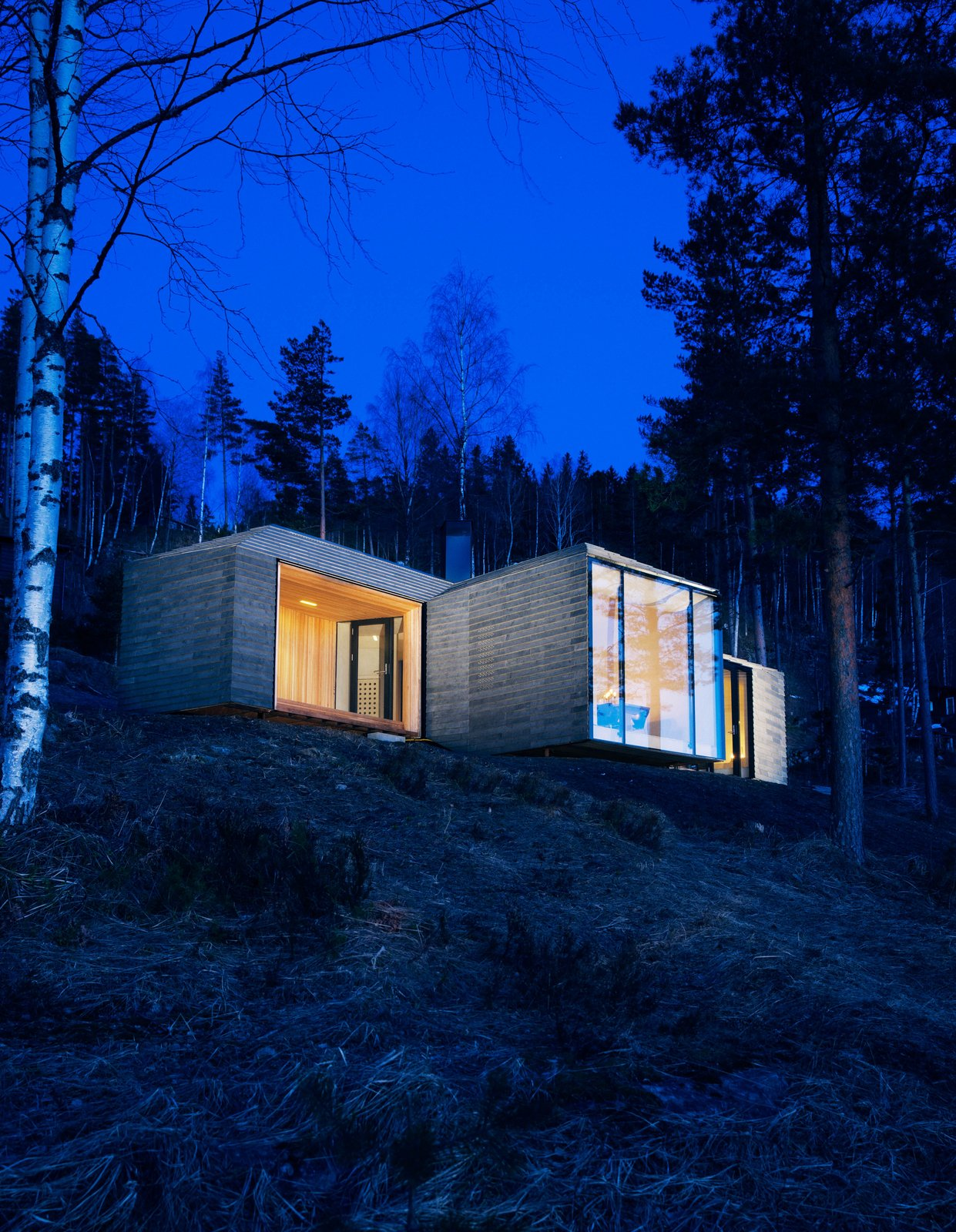 """Exterior, Cabin Building Type, House Building Type, Stone Siding Material, Flat RoofLine, and Glass Siding Material The cabin's exterior walls and roof are clad in overlapping stone plates that mimic the look of traditional wood paneling found in Western Norway. """"It provides an affinity with the cabins nearby,"""" partner and architect Nils Ole Bae Brandtzæg explains. Solar panels cover the chimney pipe, lighting LED lamps inside.  Photo 38 of 101 in 101 Best Modern Cabins from Little Homes in the Country"""