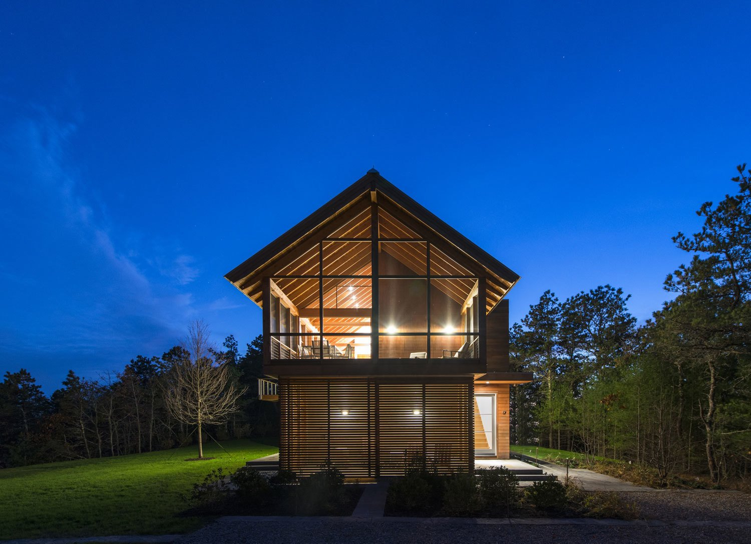 Exterior, Cabin Building Type, Wood Siding Material, House Building Type, and Glass Siding Material At night, the interior lighting casts the geometric window framing in silhouette.  Photo 37 of 101 in 101 Best Modern Cabins from Modern Gabled Cabins