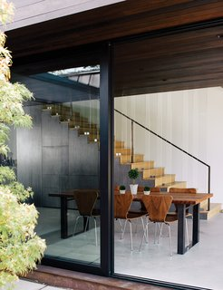 "With architect Noah Walker, principal of the Los Angeles–based Walker Workshop Design Build, homeowner Nathan Frankel has created a guesthouse high in a Beverly Hills canyon, featuring a living room that doubles as an 80-seat concert hall. The new volume houses the dining area, which includes stairs to the bedrooms. The table is from Blake Avenue and the walnut chairs are from Room & Board. ""You don't want bright colors to take away from that relationship between the interior and the exterior,"" Walker says."