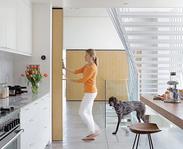 """A nine-foot-tall door covered with quarter-inch white oak slides along a ceiling rail and can be moved with just a finger to close off Don and Lisa's kitchen or bedroom. Made of wood and metal, and welded onsite, the door moves along 400-pound-capacity rollers by McMaster-Carr. A matching sliding door opposite hides a storage area. """"Because of their size, the doors had to be made inside,"""" says Don, who did the job himself."""