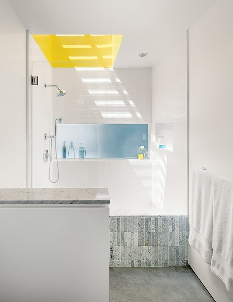 """The master bathroom has a small window and a large skylight above the shower—and shares a translucent glass expanse with the kitchen, where it becomes the backsplash. """"Even though it's a buried room,"""" Don says, """"we have three sources of natural light. For the shower, we made a very high curb so you can stop up the drain and turn it into a big soaking tub. We used white, one-by-four-inch or one-by-six-inch Carrara marble tiles from Royal Stone and Tile. They come on a 12-by-12-inch sheet. I got the small tiles because you can use them to work the bottom plane into the shower."""""""