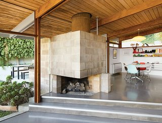 A Midcentury Home Keeps the History Alive - Photo 3 of 10 - The dining area features a distinctive cinder block fireplace. Molded plastic side chairs are arranged around a Segmented Base table, all by Charles and Ray Eames for Herman Miller. The space is illuminated by a Saucer pendant lamp by George Nelson from Modernica.