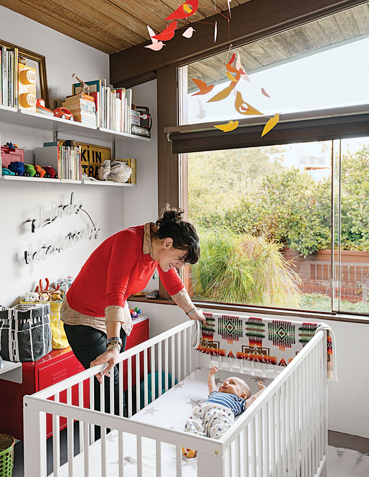 """Baby Max's bedroom (in his parents' Los Angeles A. Quincy Jones house) is outfitted with a Gulliver crib and a red PS cabinet, both from Ikea, as well as a Birds in Harmony mobile by Christel Sadde and Katsumi Komagata for the Museum of Modern Art Store. The custom """"I brake for unicorns"""" neon sign is from Let There Be Neon, a shop in New York City.  Photo 12 of 20 in 20 Cool Cribs for the Modern Baby from A Midcentury Home Keeps the History Alive"""