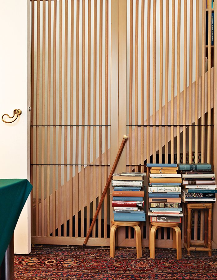 Books from Aulenti's extensive library overflow onto stools—designed by Alvar Aalto and produced by Artek—in her bedroom. The door handle, Otto A, is her own design for Fusital, from 1978.  Photo 3 of 6 in Elegant Milan Home of Designer Gae Aulenti
