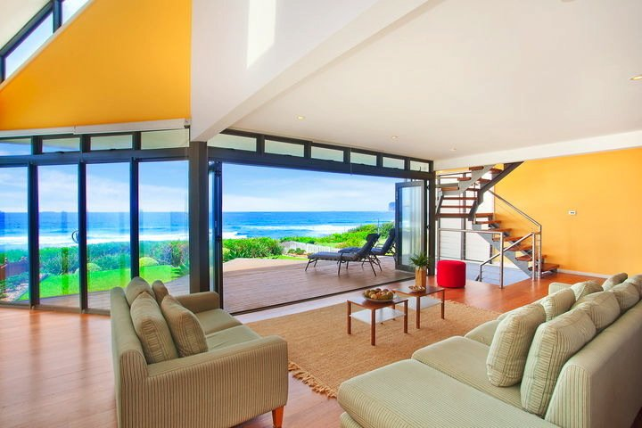 "Multi-Hued Beach Escape Near Sydney (North Avoca, Australia)  While this resort town rental is lit up with blocks of solid colors on the striking side of the Pantone scale, visitors will likely fixate on the shades of blue visible via the panoramic Pacific view. This coastal spot about 60 miles from Sydney also boasts a geometric roof and deck, further accentuating the ocean and sky awaiting outside.   Listing at ""Life is good...at the beach!""  Photo 4 of 15 in 15 Modern Summer Rentals"