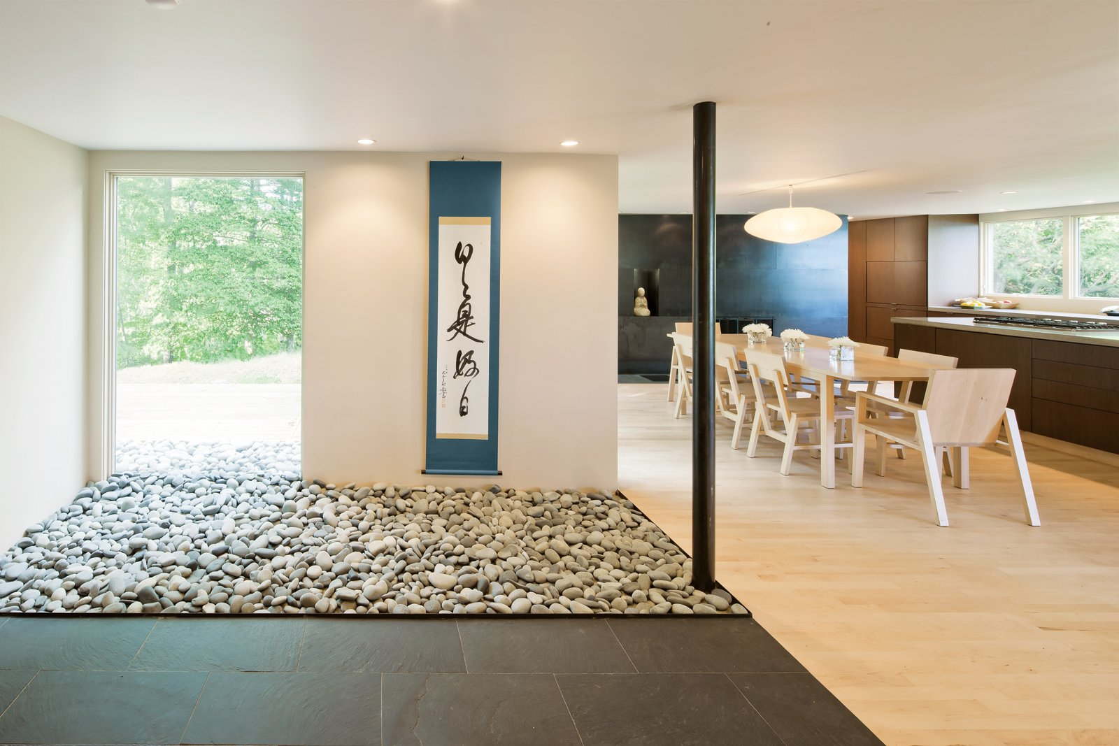 """Dining Room, Chair, Table, Light Hardwood Floor, and Pendant Lighting Stone Roses  """"We wanted to make the interior seamless with   the outdoors, and this is the first place we blur the line,"""" Katie says of the """"stone garden"""" that flows from within the entry to the deck beyond it. """"My 85-year-old father picked up the rocks at the beach, a bag or two at a time, over weeks and weeks,"""" says Scott.  Photo 4 of 5 in New McDonald"""