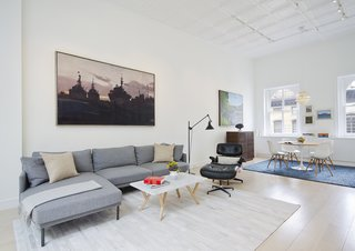 The living area now feels open and bright and showcases the couple's appreciation for furniture design and artwork. The family opted for a Camber sectional and rug from Design Within Reach, coffee table from Steven Alan Home, and replica Eames Lounge to outfit the space.