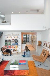 Hernandez and Surratt relax in their living room, which is enlivened by the house's internal topography. A short flight of steps divides the interconnected areas and offers a place to sit. Above is a loft that can be converted into a bedroom.