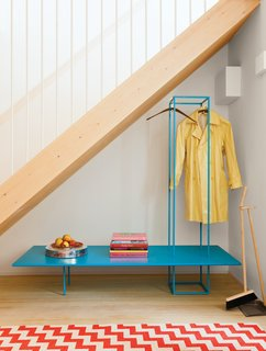 Furniture with emphasized linear elements helps prevent the appearance of clutter in small spaces. It's particularly effective when highlighted in playful colors like the blue bench storage rack in this London guesthouse.