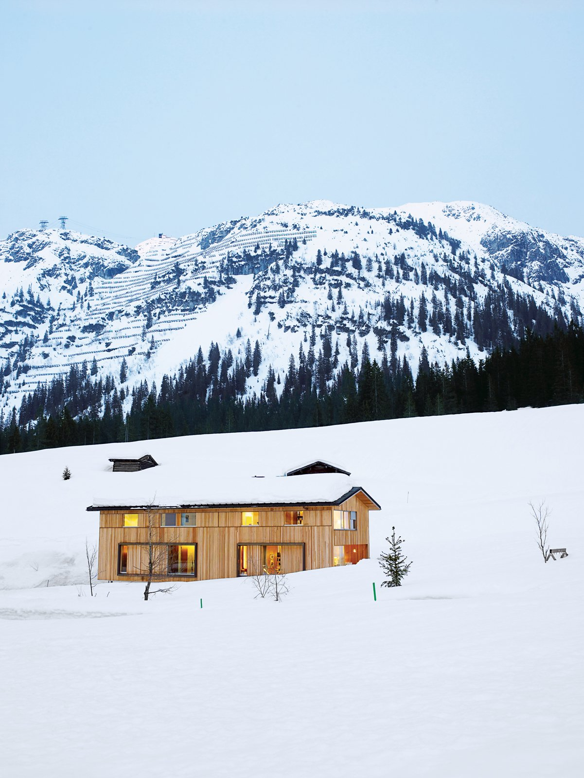 The Strolz House nestles in the winter snow at the edge of the Austrian village of Lech. Large wooden shutters help protect the windows against avalanche damage.  Photo 3 of 8 in Snow Proofed Hillside Family Home in Austria