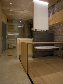 A view of the bathroom and kitchen from the main living area; the front door is at left. At right is the bench of fabricated steel, from Master Kitchen Supplies (212-533-2356). Set into a recess (with Häfele hardware) separating the maple flooring and the concrete ribbon, near left, is a table that can be used for dining, or rolled across the apartment for use as a work surface. Chan left some exposed brick on the load-bearing wall to retain what he could of the apartment's original character. Image courtesy Brian Riley.