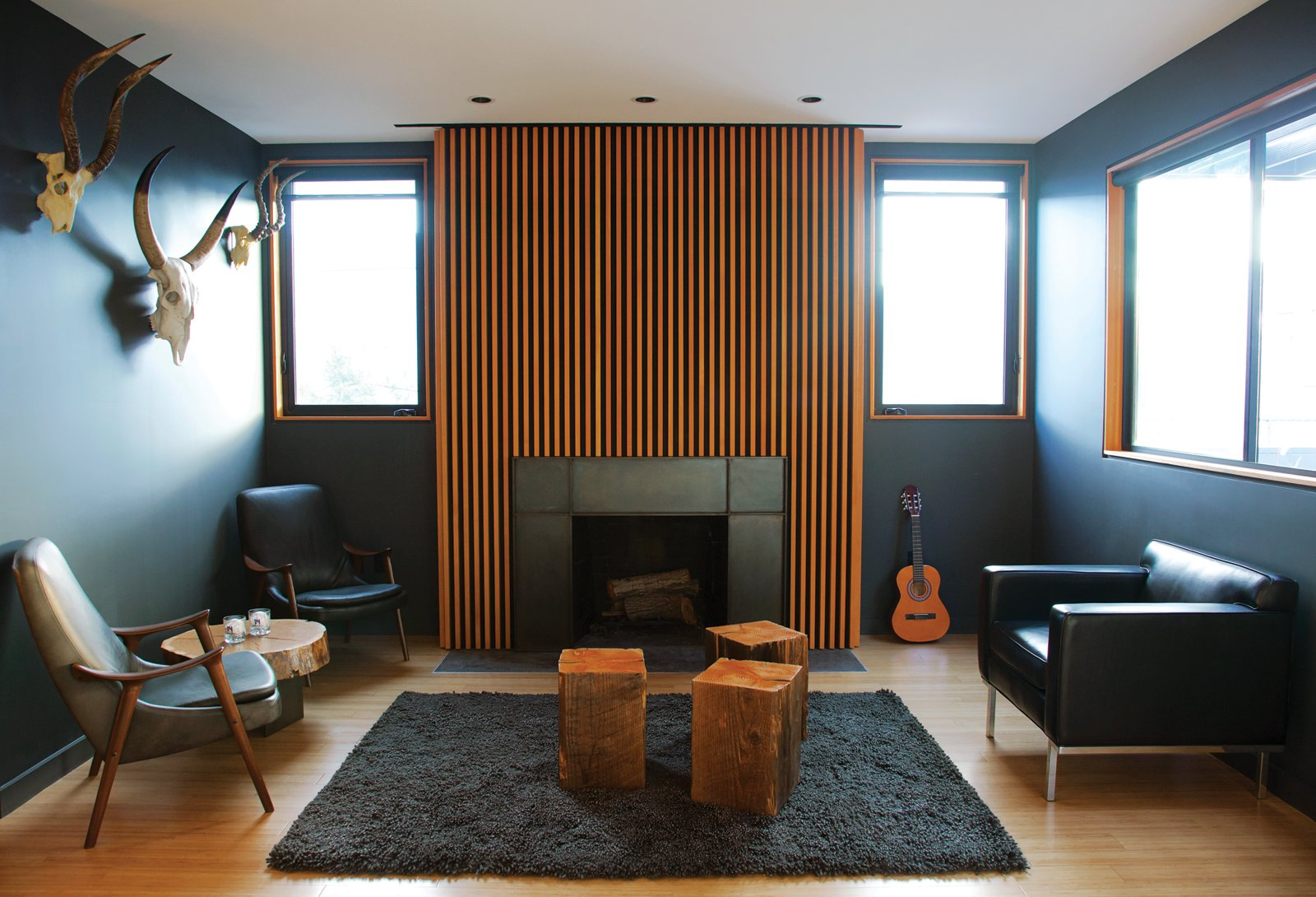 "Living Room, Wood Burning Fireplace, Standard Layout Fireplace, Chair, Rug Floor, Medium Hardwood Floor, and End Tables LOS ANGELES HOME WITH WOOD-CLAD INTERIOR  Home owner Bill Thompson warmed up his otherwise dark living room with a series of Douglas fir slats was applied above the fireplace as well as other wood accents throughout the room.  A series of Douglas fir slats was applied above the fireplace.  Photo 2 of 9 in You Won't Be Calling This House a ""Man Cave"""