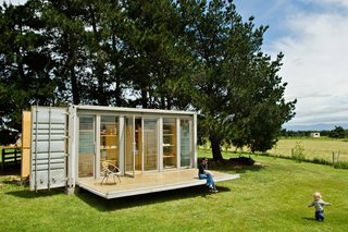 A small shipping container home in New Plymouth, New Zealand features a retractable porch.