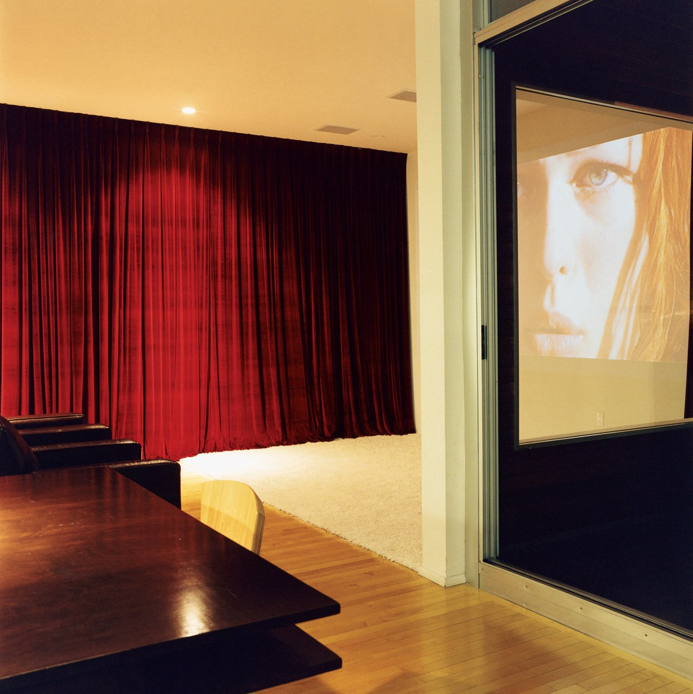 The kitchen transitions into the living room, which transforms easily into a home theater when the heavy red drapes are pulled tightly shut. The home theater system features a projector by Sharp.  Photo 7 of 11 in Making Sense of the City