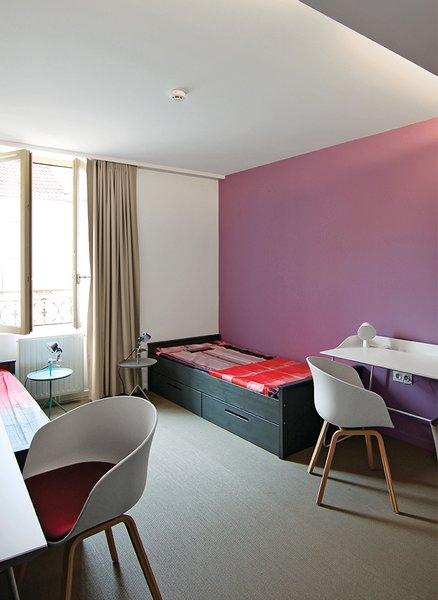How California Style Influenced a Group Home in Paris - Photo 4 of 10 - The bedrooms are furnished with Overtime desks by Stina Sandwall for Abstracta, Jim beds by File Dans Ta Chambre, and DLM tables by Thomas Bentzen for Hay. The About a Chair 22 seats by Hee Welling are covered with cushions upholstered in fabric from Kvadrat—a different shade for each room.