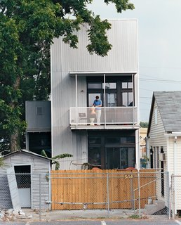 Resident Tony Vanky gets the second-story deck prepared for guests. The grittiness of the Black Pearl neighborhood is plainly visible.
