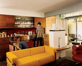 The kitchen, clad in the same wood as the joinery walls, is designed like a self-contained piece of furniture.