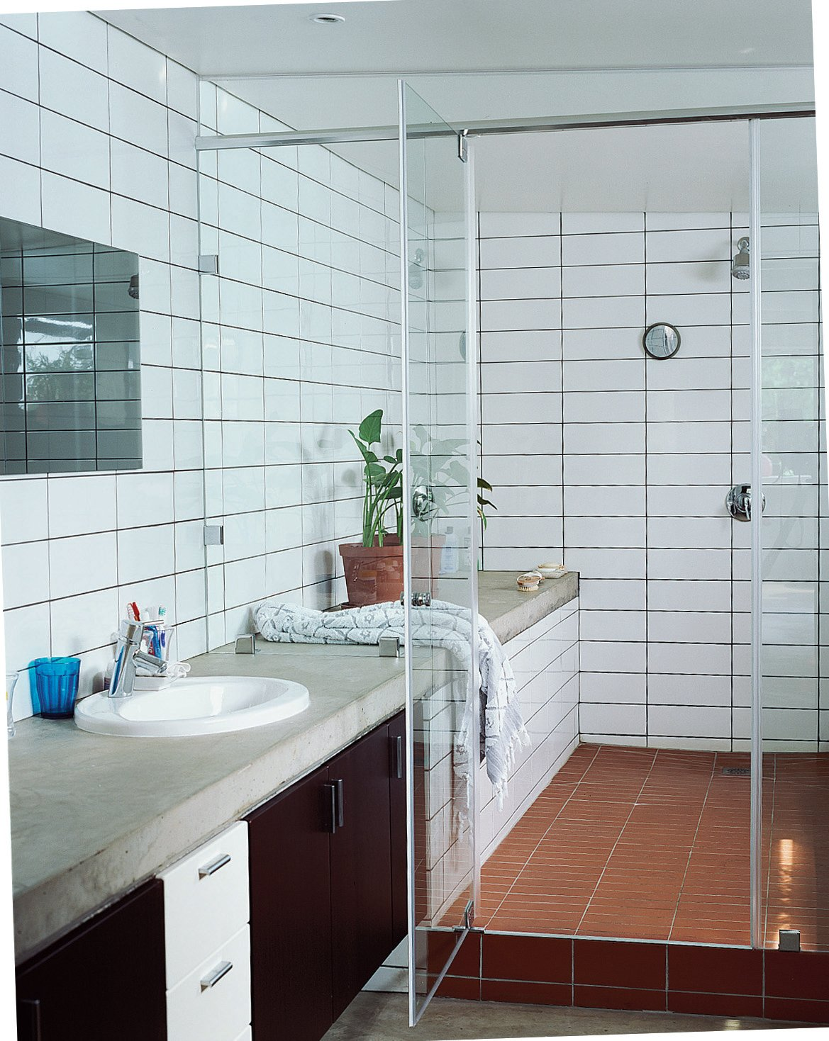 The shower-and-bath-in-one allows for the open feel of the house to translate within the bathroom. Simple concrete slabs function as countertops with inexpensive tiles laid floor to ceiling.  Photo 7 of 10 in Katz's Cradle