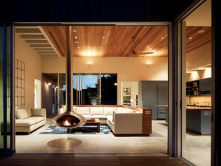 Although most radiant-heating systems are gas-powered, these ground-cement floors take the chill off with an electric warming system. Locally harvested cedar ceilings warm up the room and reach out to the matching siding, which was finished with a nontoxic bleaching oil to first speed, then arrest, the natural fading process.