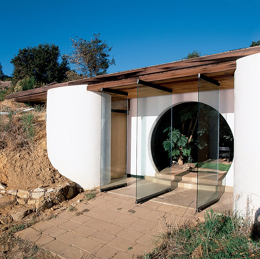Exterior, House Building Type, and Stucco Siding Material The glass doors of Muennig's own home allow the ocean breeze through the circular entry of the sea-facing front.  Photo 6 of 9 in Big Sur: Coastal Commissions