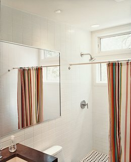 Take Me Home - Photo 6 of 7 - A brightly striped shower curtain lends bright punctuation to an otherwise austere bathroom.