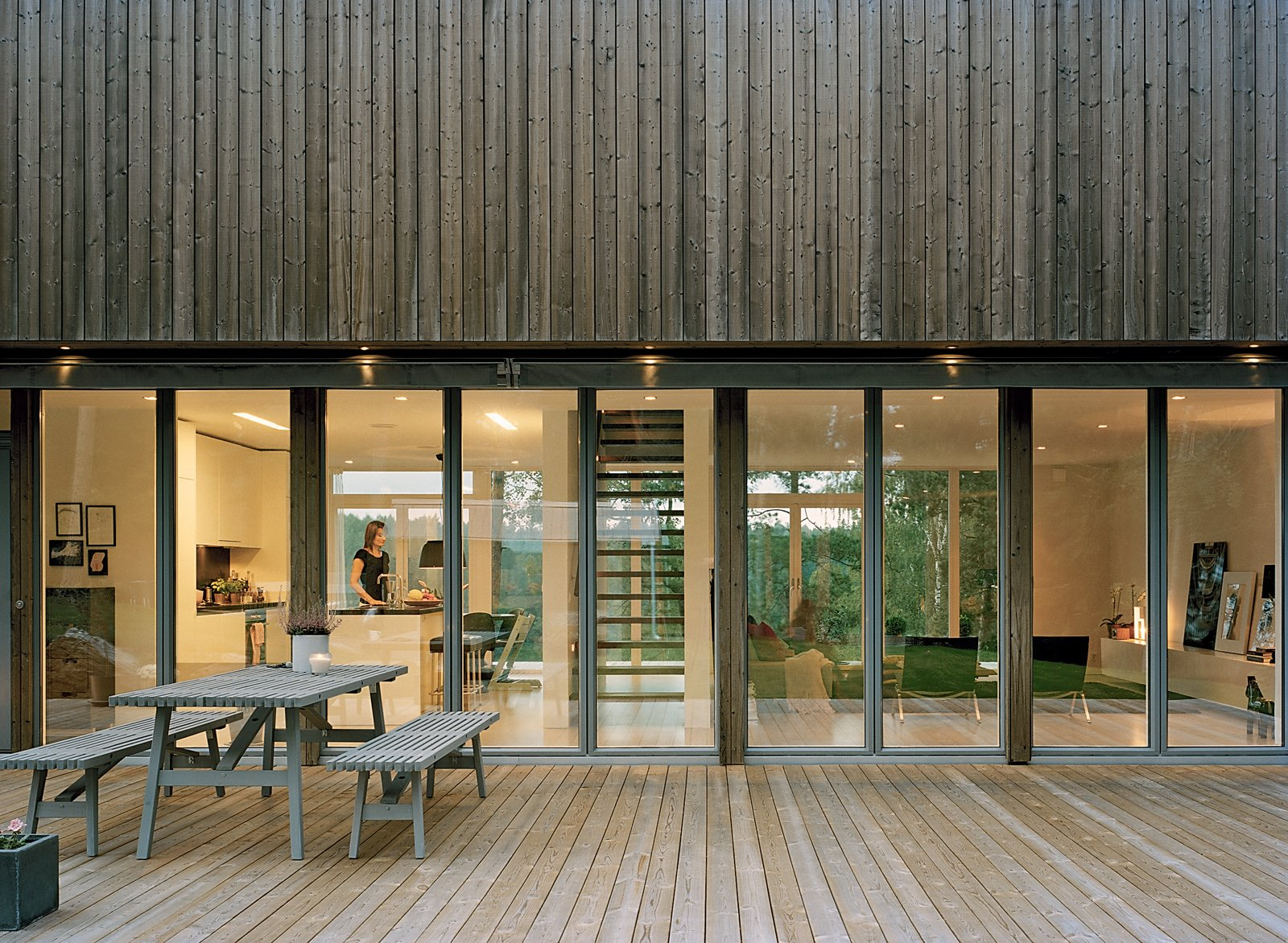 """Outdoor, Wood Patio, Porch, Deck, Large Patio, Porch, Deck, and Back Yard The spruce panels that coat the second-floor exterior will fade in tandem with the zinc-coated steel that rims the glazed windows and doors. """"They will go gray like we do,"""" says Claesson.  Photo 6 of 13 in Sum of Its Parts"""