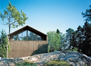 Sum of Its Parts - Photo 7 of 12 - The pitched facade has a sculptural play of spruce siding and triple-glazed windows that reflect the surrounding treetops.