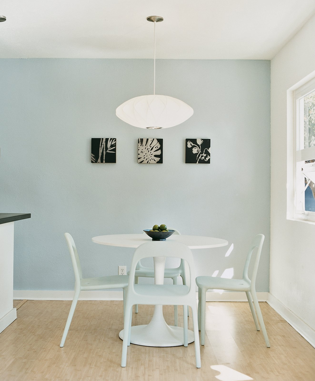 Due to the tight budget, the fixtures and furnishings had to be a mix of high and low. Instead of a Saarinen Tulip table for the dining room, they found a similar style with matching chairs from Ikea, then hung a George Nelson lamp overhead. Tagged: Dining Room, Chair, Table, and Pendant Lighting.  Photo 4 of 6 in Affordable Modern House Built with Sheer Determination