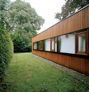 Only the rear of the house suggests the building's earlier incarnation as a 1960s bungalow, and even here the original brickwork is obscured by wood cladding.