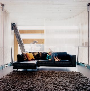 The hanging living room gains greater privacy via a gauzy curtain wall.