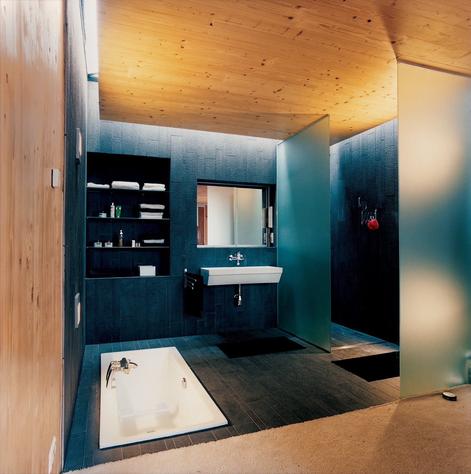 Bath Room, Drop In Tub, Wall Mount Sink, and Dark Hardwood Floor The master bathroom is softly lit by a skylight. The bath, by Laufen, is sunk into the floor to maintain a feeling of space.  Photo 8 of 10 in A Suspended Living Room Floats Like an Air Ship