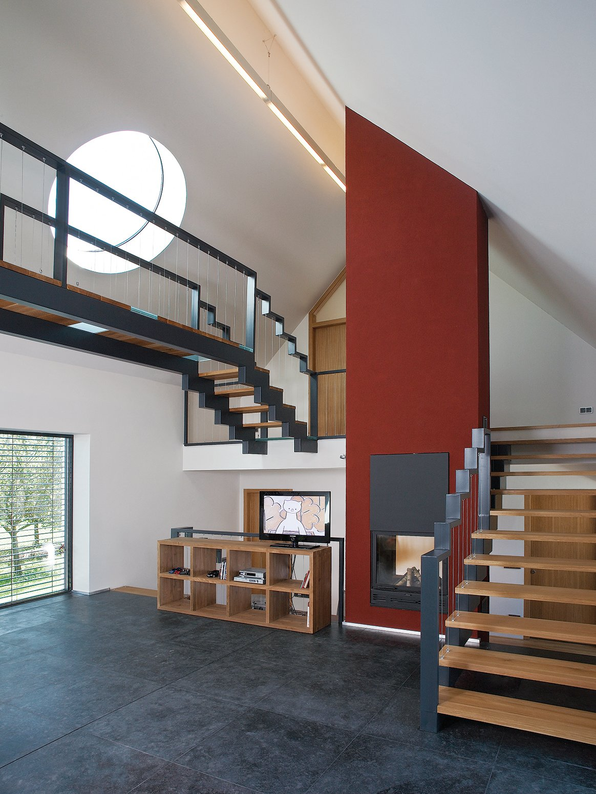 "Staircase, Metal Railing, and Wood Tread Circular ""sun disks"" cut into the slanted roof create light shafts that move throughout the day, casting angular shadows as they pass over the steel staircases and catwalk.  Photo 2 of 4 in A Striking Bohemian Geothermal Home"