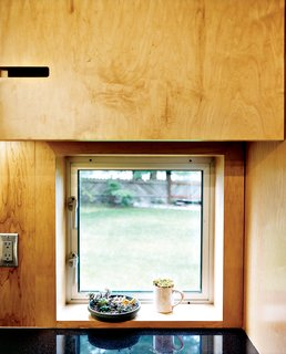 Geometric notches in the kitchen cabinetry are simple and cost-effective substitutes for metal cabinet pulls—they also provide visual interest in an otherwise unadorned space.