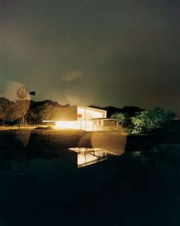 At night, the entire studio glows like a lantern, its light amplified by the reflection in the seasonal pond.
