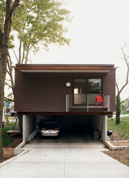 Exterior, House Building Type, Flat RoofLine, and Mid-Century Building Type A rear view of the garage and the deck off the master bedroom.  Photo 7 of 9 in Affordable, SIP-Built Family Home in Kansas City