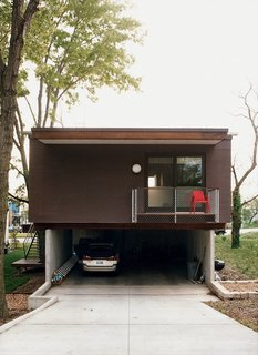 A rear view of the garage and the deck off the master bedroom.