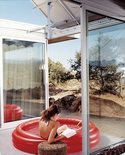 """The living space and bedrooms are separated by two small courtyards. Linda Taalman reclines in a small, inflatable wading pool in the home's """"firecourt,"""" facing south toward the desert."""
