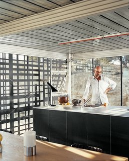 """All kitchen appliances, cupboards, and counters have been united in a single, self-contained island, designed in collaboration with Bulthaup. The architects wanted unfussy space and they rejected easy-access overhanging cabinets. """"There's an emphasis on convenience in the world that is all about numbing things,"""" says Alan Koch."""