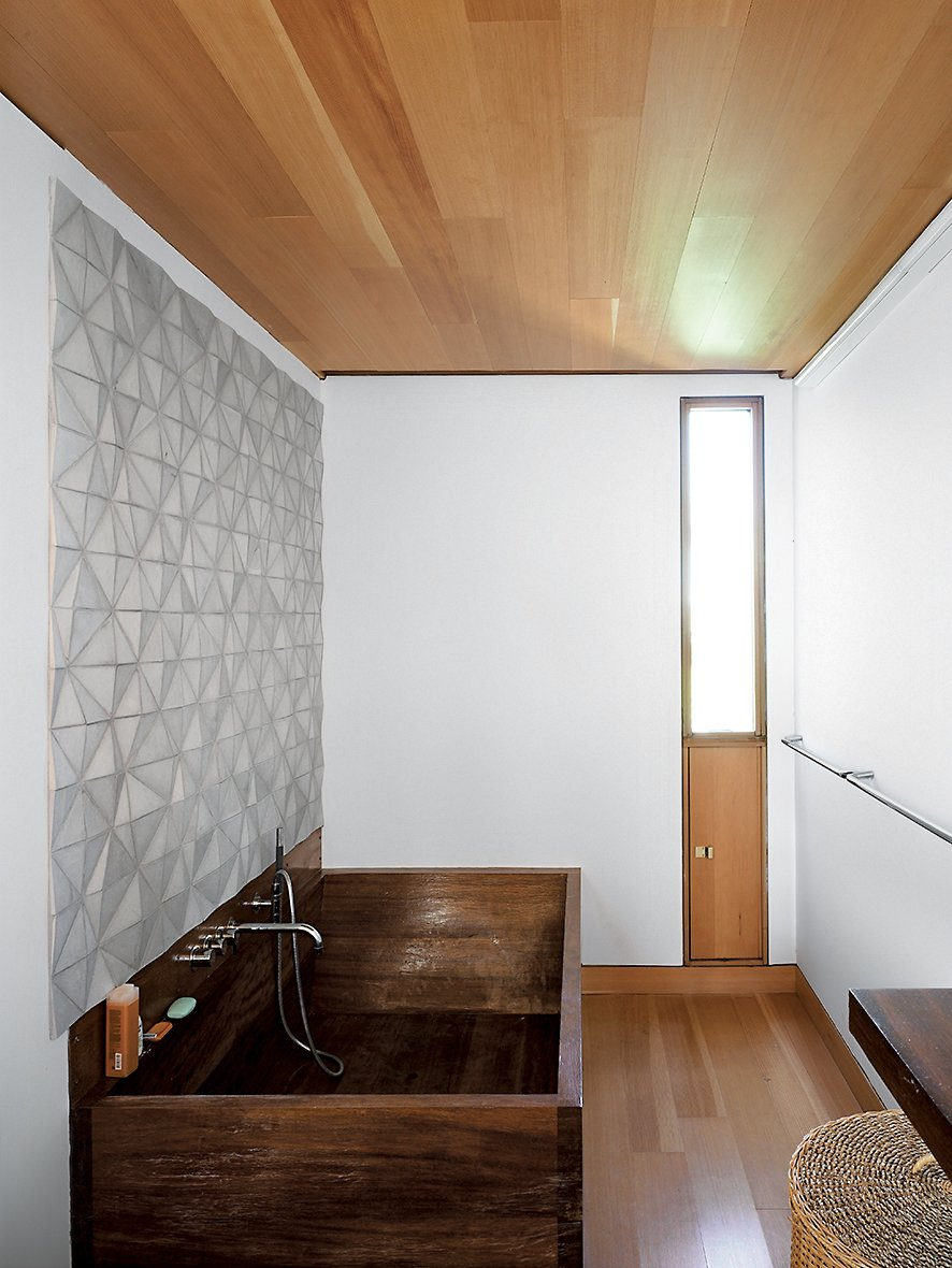 Bath Room, Soaking Tub, Freestanding Tub, Medium Hardwood Floor, and Ceramic Tile Wall In the bathroom, a custom ceramic backsplash designed by Meredith and Sample joins an iroko-wood tub created by their students a the University of Toronto.  Photo 10 of 16 in Floating House, Lake Huron